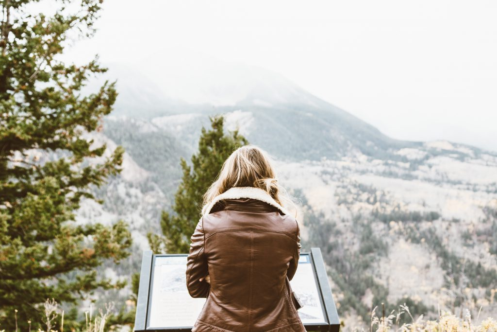 back photo of woman wearing black leather jacket in front of snowed mountain